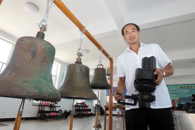 范永君手里拿的是现代火车的汽笛装置,而老式火车用的是他身旁的铜铃.图片